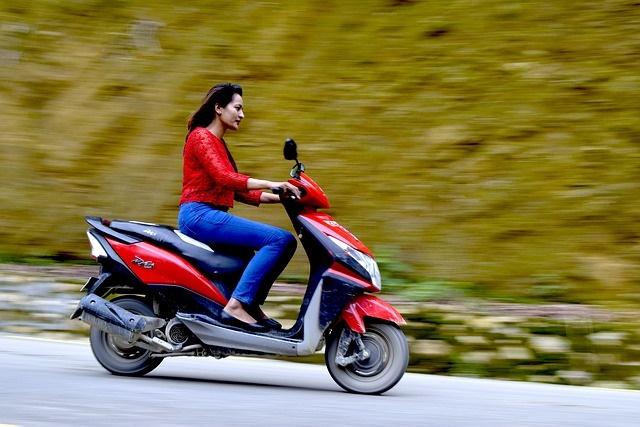 Chica conduciendo scooter eficiente por Ibiza